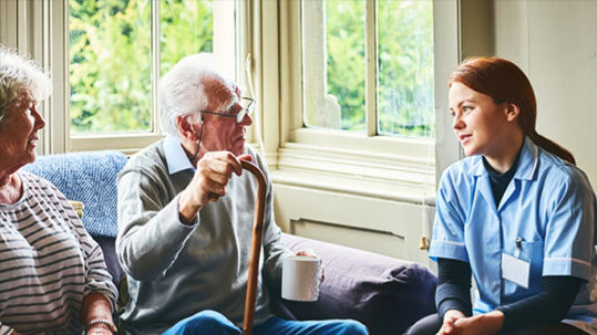 Elderly couple talking to a carer