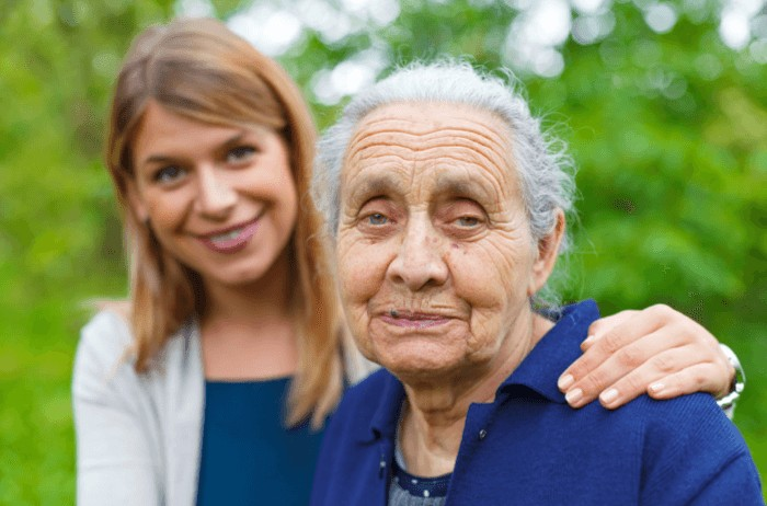 Elderly lady and carer, carer's arm is around the elderly lady's shoulder.