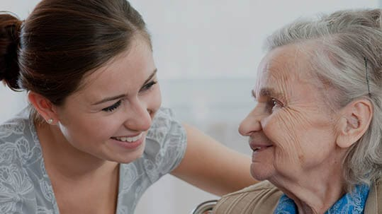 Elderly lady with carer, both smiling