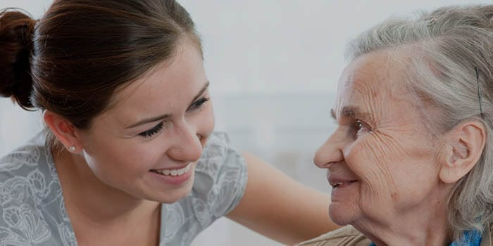 Elderly lady with a carer, both smiling