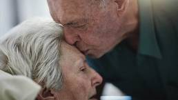 Elderly lady in Pallative Care being kissed by her husband on the forehead